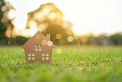 Closed up tiny home model on green grass with sunlight background.