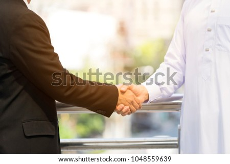Closed up two businessman making handshake to promise their business collaboration and trusting a commitment to develop the energy, gasoline investment. Technology innovation sharing together.  #1048559639
