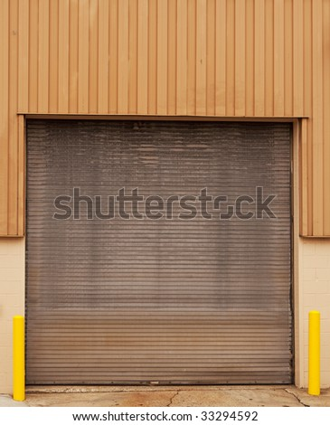 closed warehouse door with yellow posts