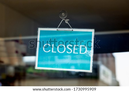 Closed white sign on turquoise blue background banner placed on the glass door. Concept of closed business, lockdown due to Covid-19 2020 crisis and bankruptcy. Stock photo ©