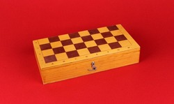 Closed wooden chess board on red background