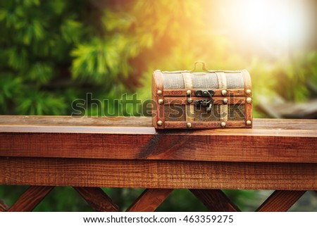 Closed wooden chest box outdoors in nature. Selective focus, lens flare.