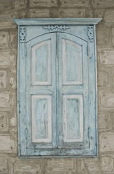 Closed, wooden Old window with podertoy blue paint on the background of cement tiles, a window with wood carvings