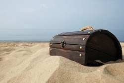 Closed wooden treasure chest on sandy beach, space for text
