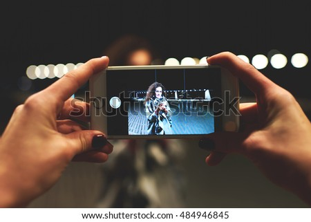 Closely image of female hands holding mobile phone with photo camera mode on the screen.Cropped image of hipster girl shooting video of friend with cell telephone while standing outdoors in night time
