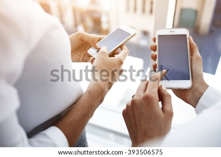 Closely image of woman`s hand is holding cell telephone with copy space screen for your advertising text message, while her friend near dials the number on smart phone. Two female are using cellphones