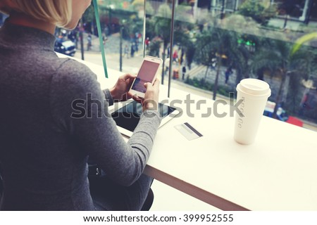 Closely of woman is typing text message on cell telephone, while is resting in coffee shop of modern shopping center in New York. Young hipster girl is chatting in social network via mobile phone