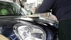 Closely shown as a professional worker polishes the transport (car) body using a polishing tool (machine). Concept from: Auto service, Car Painting, Machine washing.