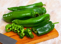 Closeout of chopped organic green sweet pepper on wooden background. Healthy nutrition concept
