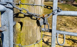 closer look at two galvanised steel farm gates chained together by rusting padlock via a substantial round wooden post with barbed wired wrapped around it