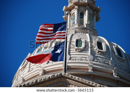 closer look of the Texas state capitol building's dome with waving flags of the United States and Texas