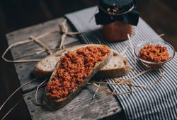 Closer view of slices sourdough, rye bread with ajvar spread on them. Sourdough bread placed on a wooden surface.