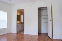 Closet and bathroom through doors in bedroom