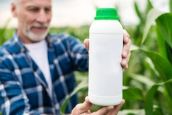 Closeup a bottle with chemical  fertilizers in the hand's of middle aged farmer standing in a field.  Fertilizer bottle mockup