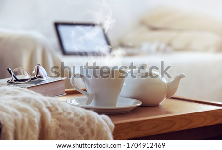 Closeup a teapot, cup of tea with steamon on the wooden coffee table. Laptop on the sofa for work. Still life from home interior of living room. Remote learning or work. Break time concept. Foto stock ©