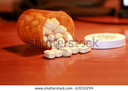 closeup aka macro shot of white pills spilling out of a orange plastic pill bottle on a table. This powerful image can represent, medication, over dose, drug abuse, addiction, medical help, and more