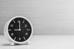 Closeup alarm clock for decorate in 9 o'clock on wood desk and wall textured background in black and white tone with copy space