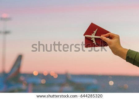 Closeup an airplane model toy and passports at the airport background big window at dawn - Shutterstock ID 644285320