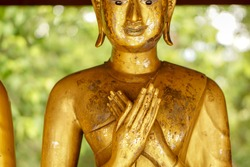 Closeup and crop front view of old and golden Buddha statue in muse action (In his standing posture Both hands lifted up. Sitting at the Ura His right hand overlaps the left hand. As a muse)
