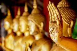 Closeup and crop hand of golden Buddha statue with a gold leaf on blurred golden Buddha statue stand strong line background
