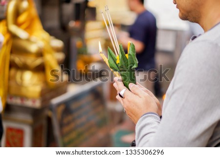 Closeup and crop hands of Asian young man holding a incense and flower cone with candle burned and pay homage to worshiping the Buddha at the Thai temple on the end of the year.