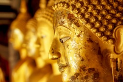 Closeup and crop old and golden face of golden Buddha statue on blurred golden Buddha statue stand strong line background