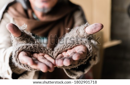 Closeup and focus dirty hands of poor man beggar. Old homeless man with gray beard wear gloves with sitting and hands up for help and food beggar because hungry. Help and hope concept. Foto stock ©