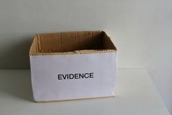 Closeup and selective focus on EVIDENCE sign attached to cardboard box placed on wooden table with sunlight and shadow