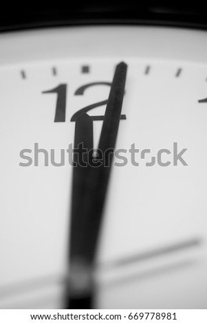 Closeup and selective on the pointers of a clock marking a minute after midnight - black and white rendering. The main focus is on the number twelve and its pointer.  #669778981