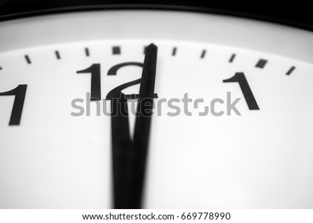 Closeup and selective on the pointers of a clock marking a minute after midnight - black and white rendering. The main focus is on the number twelve and its pointer.  #669778990