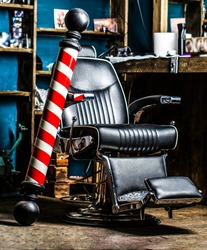 Closeup armchair. Barber shop pole. Logo of the barbershop, symbol. Stylish vintage barber chair. Barbershop armchair, hairdresser, hair salon, barber shop for men.