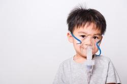 Closeup Asian face, Little children boy sick he using steam inhaler nebulizer mask inhalation oneself on white background, health medical care