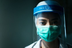 Closeup Asian female Doctor wearing face shield and PPE suit for Coronavirus outbreak or Covid-19, Concept of Covid-19 quarantine