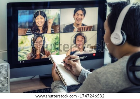 Closeup Asian man hand writing notebook when online learning via video conference with colleague and team building meeting when Covid-19 pandemic,Coronavirus outbreak,online meeting,new normal concept
