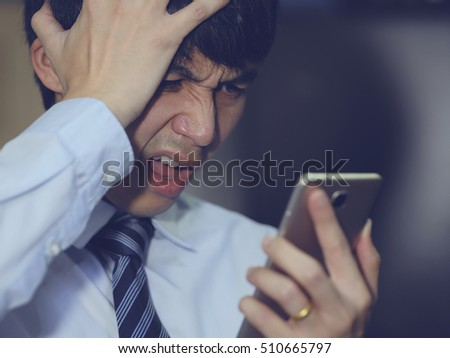 Closeup Asian portrait shocked, displeased, angry, young company businessman unhappy by what he sees on cell phone, Negative human emotion facial expression feeling. Breaking news