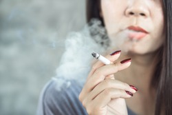closeup Asian woman hand smoking cigarette ,unhealthy lifestyle concept