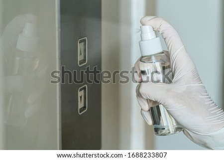 Closeup Asian woman hand wearing medical gloves and spraying Anti-Bacterial Sanitizer Spray to the elevator button before cleaning press, Coronavirus Network Outbreak,health care and cleaning covid19