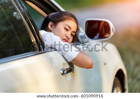 Closeup asian women of a worried car looking at side through the window in a sad day