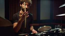 Closeup attractive man hand twirling drumstick in hand in concert hall. Band drummer preparing to play drum kit in recording studio. Handsome musician turning drumstick in hand at music studio.