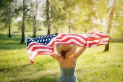 Closeup back view of a Proud woman enjoying summer sunset outdoors and holding american flag
