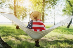 Closeup back view of a Proud woman enjoying summer sunset outdoors and holding american flag. Relax on a hammock in the Park.
