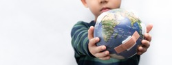 Closeup banner of a cute little asian boy a new generation presenting a damage globe full of bandages. Global warming, Climate change, Environmental problems. World pollution, Earth day, April 22.