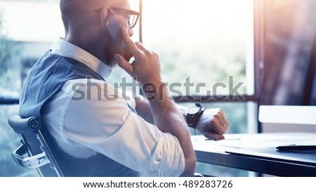 Closeup Bearded Businessman Wearing White Shirt Waistcoat Working Modern Loft Startup Computer.Creative Young Man Using Mobile Phone Call Partner Meeting.Gentleman Guy Looking Watch Workplace.Blurred Stockfoto ©