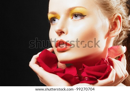 closeup beautiful blonde woman with leaf of red rose. Creative make-up.