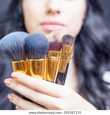 Closeup beautiful woman Arab appearance in the beauty salon with a nice makeup. Holding in hands a set of professional makeup brushes on a dark or black background.