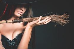 Closeup beautiful woman like witch holding broom. Fashion. Halloween costumes