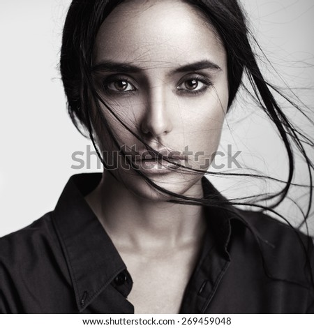 Closeup beauty portrait of a young sensual beautiful brunette girl with long black straight flying hair. Smoky eyes.