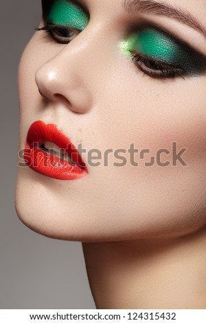 Closeup beauty portrait of attractive model face with bright visage. Chic green eye makeup and red lips make-up