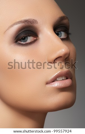Closeup beauty portrait of attractive model face with fashion visage. Dark smoky eye makeup and beige gloss lips make-up - stock photo