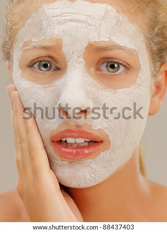 closeup beauty portrait of beautiful blonde woman with a facial mud mask on her skin, touching her face, with worried face expression